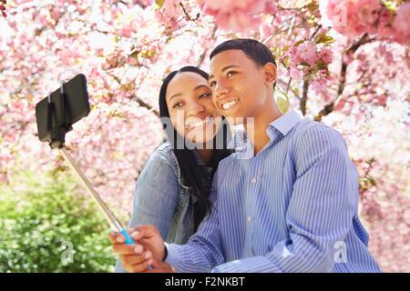 Les amis taking self portrait en vertu de l'arbre en fleurs Banque D'Images