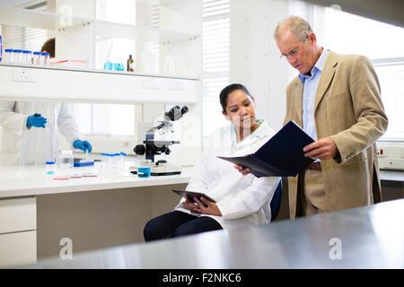Homme d'affaires et expert scientifique en laboratoire en conversation
