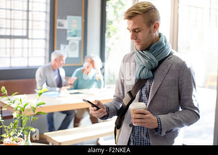 Businessman using cell phone in office Banque D'Images