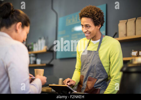 Mixed Race barista assisting customer in coffee shop Banque D'Images