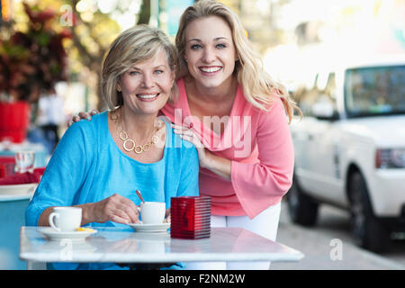 Caucasian mother and daughter drinking coffee at sidewalk cafe Banque D'Images