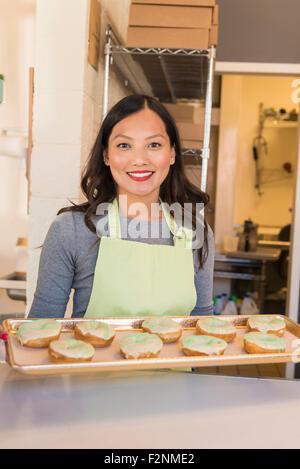 Asian baker holding tray of donuts en boulangerie Banque D'Images