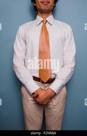 Jeune homme debout par un mur bleu, il porte une cravate Banque D'Images