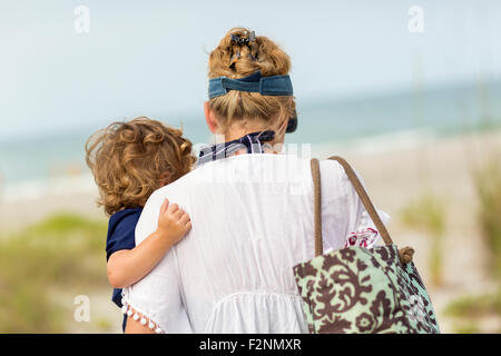 Caucasian mother carrying baby son on beach Banque D'Images