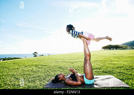 Mother holding daughter avec jambes en park Banque D'Images