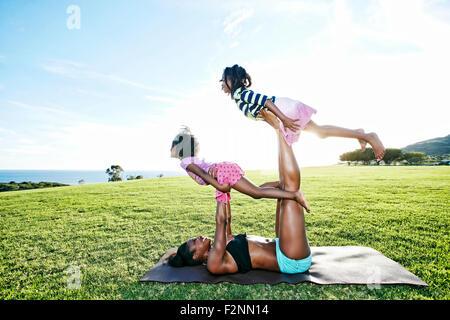 Mère tenant les enfants sur un tapis de yoga in park Banque D'Images