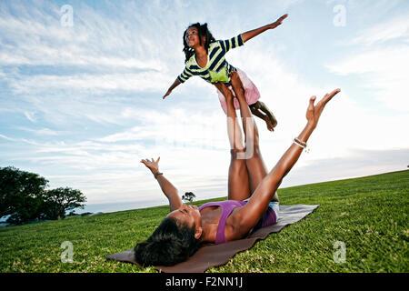 Mère Fille d'équilibrage sur les jambes dans le parc Banque D'Images