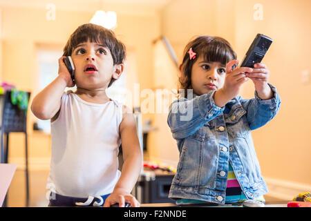Frère et sœur jouant avec téléphone cellulaire et commande à distance Banque D'Images