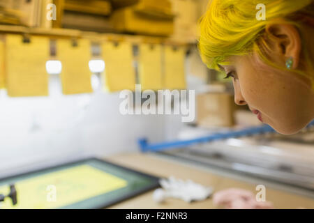 Caucasian artist travaillant dans l'atelier d'impression écran Banque D'Images