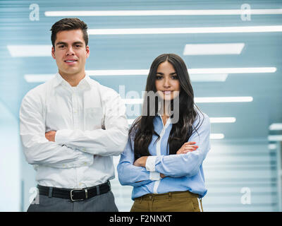 Business people standing with arms folded in office Banque D'Images