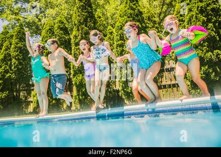 Les enfants de sauter dans une piscine Banque D'Images
