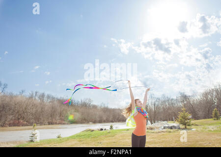 Caucasian girl Playing with ribbons in park
