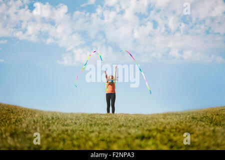 Caucasian girl Playing with ribbons sur colline