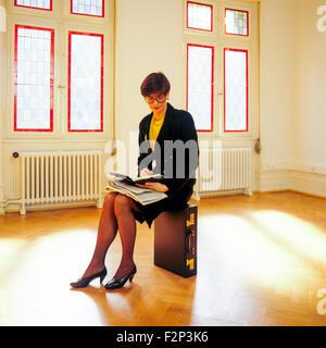 Recherche et offres d'assis sur son porte-documents dans une salle vide Banque D'Images
