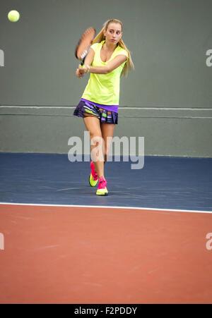 Jeune femme jouant au tennis dans un centre de tennis intérieur Banque D'Images