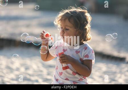 Petite fille faisant des bulles de savon à l'aire de jeux Banque D'Images