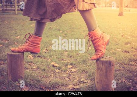Une femme est joyeusement marcher sur certains petits poteaux de bois dans le parc