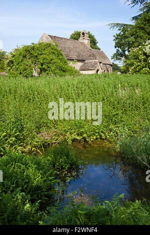L'Ampney Brook qui traverse l'église romane de St Mary dans le village de Cotswold Ampney St Mary, Gloucestershire Banque D'Images