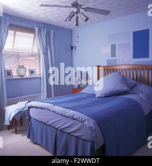 Ventilateur de plafond dans la chambre à coucher de style économique à thème bleu Banque D'Images
