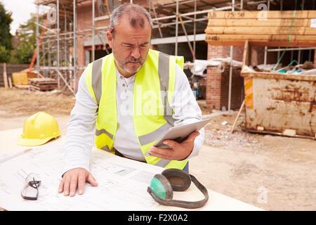 Construction Worker Using Digital Tablet sur chantier Banque D'Images