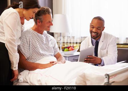 Doctor Talking to patient de sexe masculin et la femme in Hospital Bed Banque D'Images