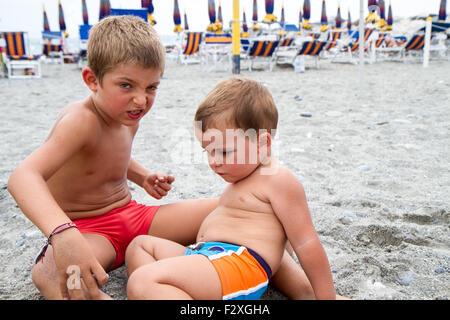 Deux petits frères jouant sur la plage Banque D'Images