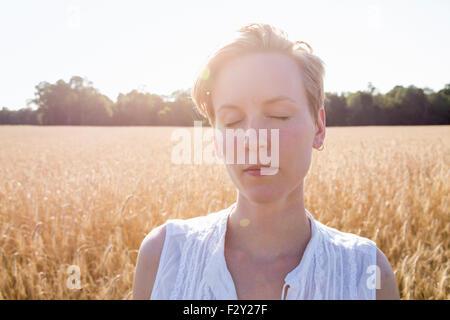 Head and shoulders portrait d'une jeune femme debout dans un champ de maïs. Banque D'Images
