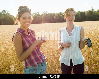 Deux jeunes femmes souriant debout dans un champ, l'un tenant un téléphone intelligent. Banque D'Images