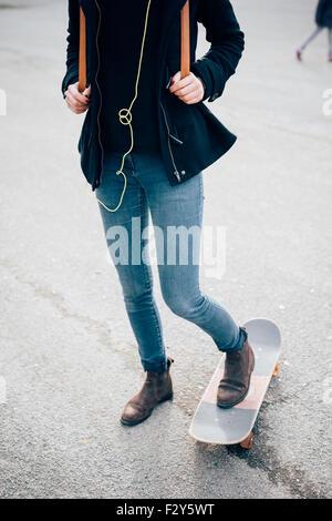 Gros plan sur les jambes avec les pieds sur la planche à roulettes d'une belle jeune femme sportive hipster - sport, des moyens de transport de concept
