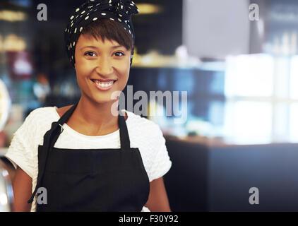 Jeunes business owner standing dans son café-restaurant dans un tablier et bandana smiling at the camera