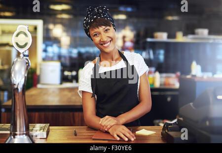 Accueil chaleureux accueil de jeunes entrepreneur debout derrière le comptoir dans son café en donnant l'appareil Banque D'Images