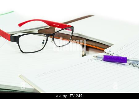 Verres sur des livres avec un stylo sur fond blanc Banque D'Images