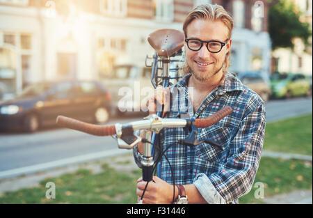 Jeune homme. Le mode de vie urbain vélo transportant sur son épaule. smiling portrait Banque D'Images