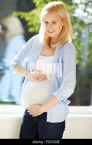Femme enceinte, sentant son bébé bouger Banque D'Images