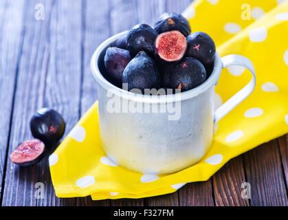 Figues fraîches dans la tasse du métal et sur une table Banque D'Images