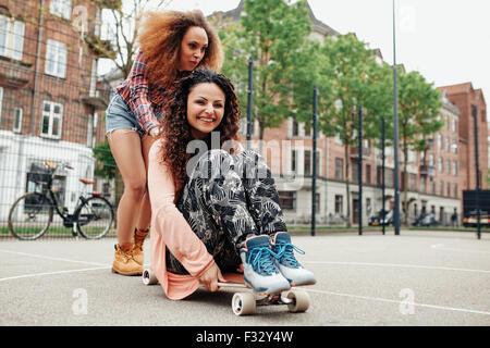 Tourné en plein air de deux professionnels des jeunes femmes jouant avec longboard. Jeune femme assise sur longboard Banque D'Images