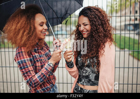 Les jeunes amis ensemble debout contre une clôture dans la ville la consommation de crème glacée. Deux femmes avec Banque D'Images