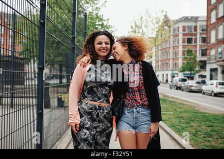 Heureux les jeunes femmes à marcher le long de la rue de la ville. Femme amis ensemble en plein air dans la ville, Banque D'Images