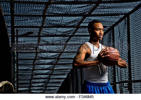 Un jeune homme pose avec un terrain de basket-ball. Banque D'Images