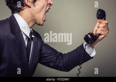 La colère du jeune homme est au téléphone et crier Banque D'Images