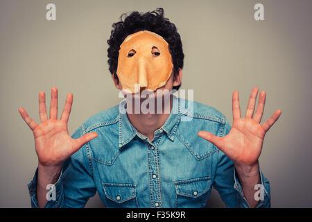 Jeune homme a coupé en orbites une crêpe et porte sur son visage Banque D'Images