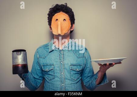 Jeune homme a coupé en orbites une crêpe et porte sur son visage tout en maintenant un pot de café Banque D'Images