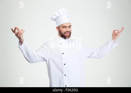 Portrait of a happy chef cuisinier montrant le geste de bienvenue isolé sur fond blanc