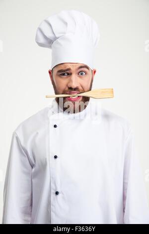 Portrait of a handsome male chef cook holding spoon en dents isolé sur fond blanc Banque D'Images