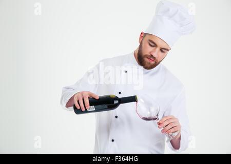 Portrait of a male chef cuisinier de verser le vin en verre isolé sur fond blanc Banque D'Images