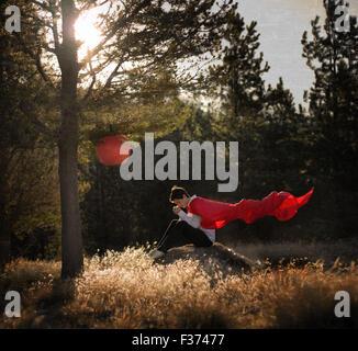 Garçon avec une casquette rouge de l'emplacement dans une colline dans la forêt Banque D'Images