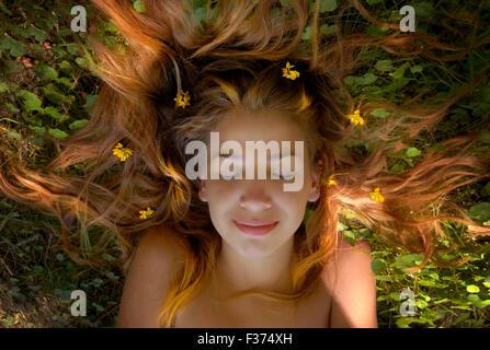 Belle fille blonde cheveux longs dans l'herbe avec des fleurs dans la tête Banque D'Images