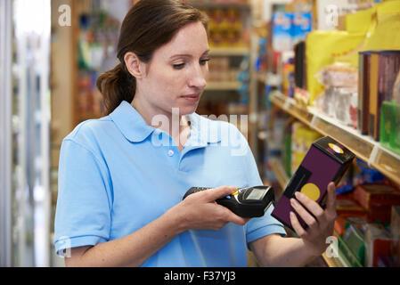 Sales Assistant Contrôle de niveaux de stock dans l'aide de dispositif portable Supemarket Banque D'Images