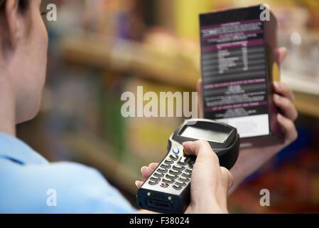 Sales Assistant Contrôle de niveaux de stock dans Supmarket en utilisant l'appareil à main Banque D'Images