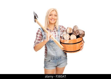 Jeune femme blonde en chemise à carreaux tenant un seau plein de billes et de transporter une hache à l'épaule